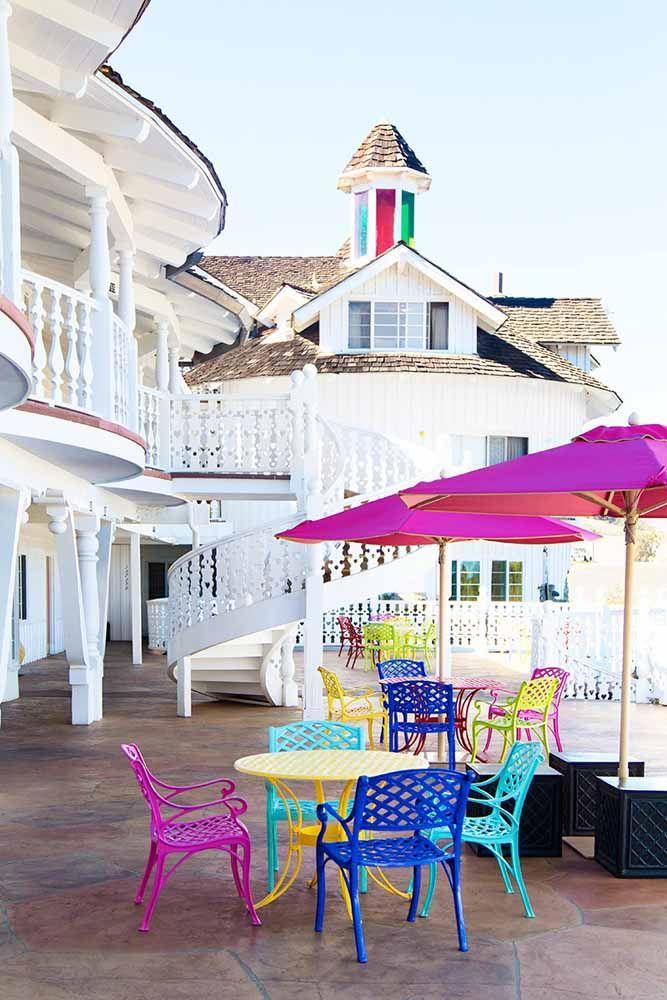 A fachada da casa toda branca ganhou ombrelones, mesas e cadeiras de cores intensas e contrastantes