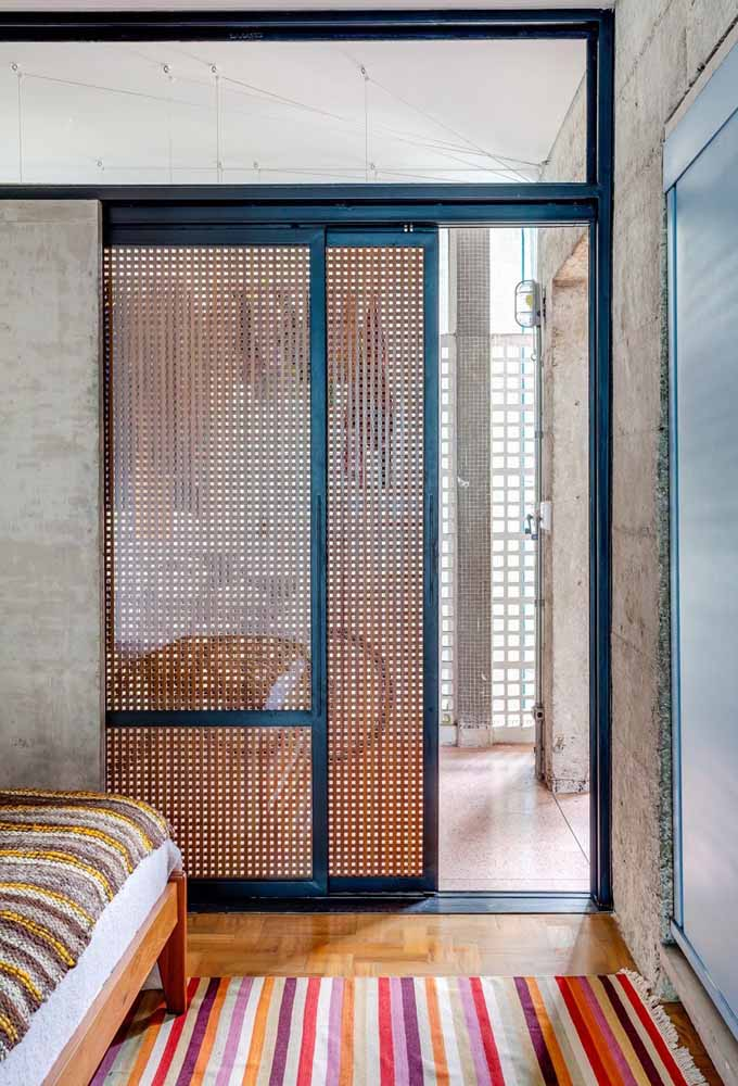 De design diferenciado, essa porta de correr traz uma tela de madeira para garantir um pouco de privacidade para o interior do closet