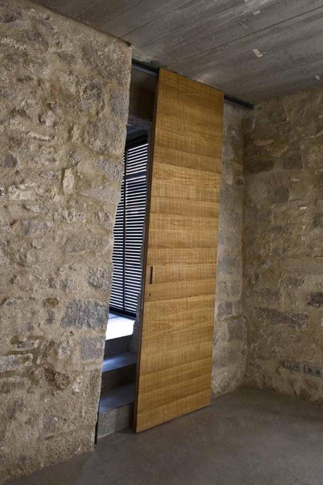 A porta de madeira em ângulo segue o recorte da parede de pedra; um projeto original e moderno