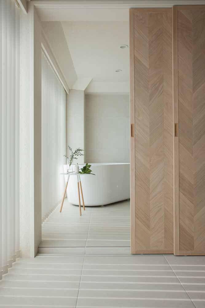 Entre o quarto e a suíte uma glamourosa porta de correr de madeira