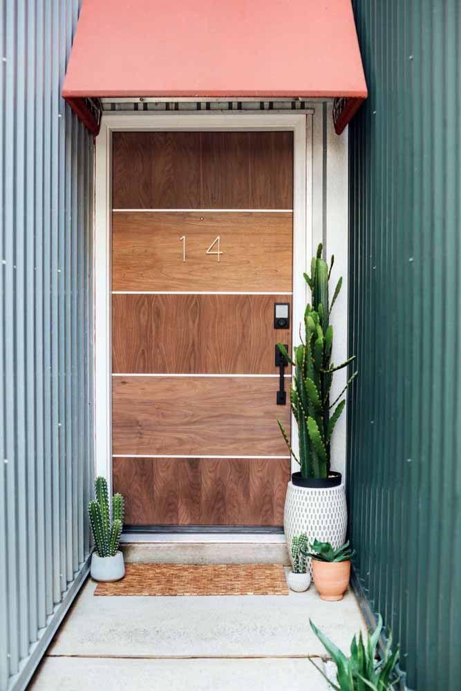 Faixas de diferentes tipos de madeira compõe essa porta de entrada