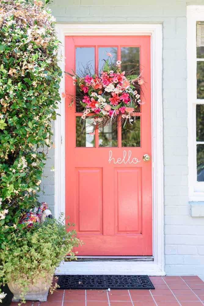Uma charmosa e romântica porta cor de rosa decorada por uma guirlanda de flores
