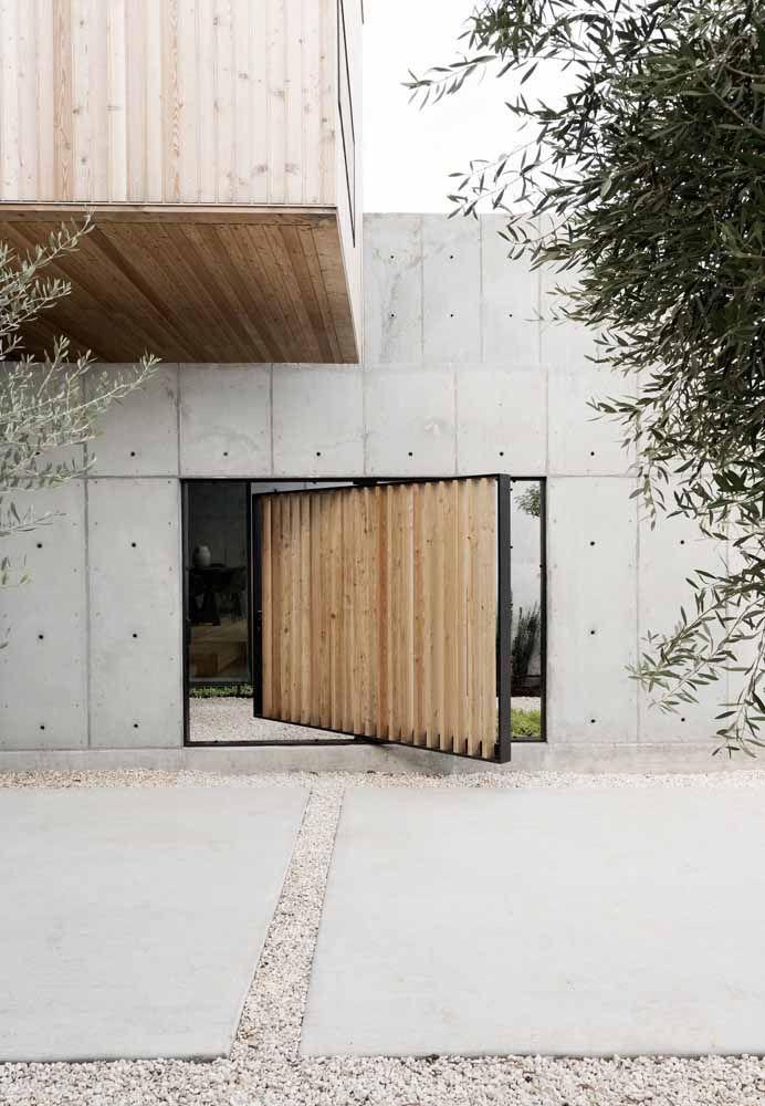 A parede de concreto aparente ganhou uma porta de madeira pivotante bem diferente