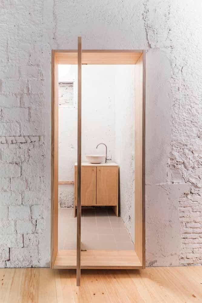 A porta pivotante causa um forte efeito de contraste entre o rústico da parede e a elegância da madeira