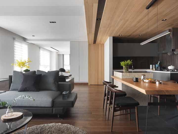 Nesse ambiente integrado, o teto rebaixado de madeira dá vida a porta