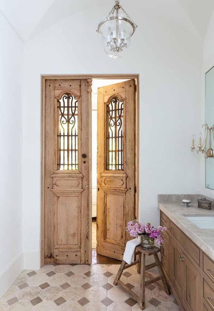 Rústica e colonial: essa porta de duas folhas é o grande destaque do banheiro