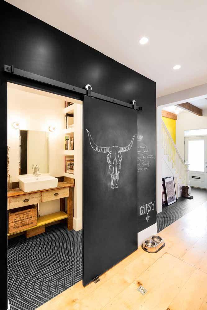 Nessa casa, a entrada do banheiro foi feita com tinta lousa