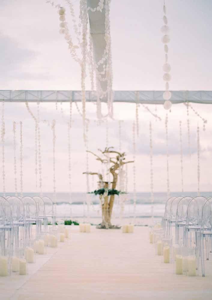 Cadeiras de acrílico, velas e cortinas de madrepérola decoram o caminho até o altar: a cerimônia não poderia ser mais delicada