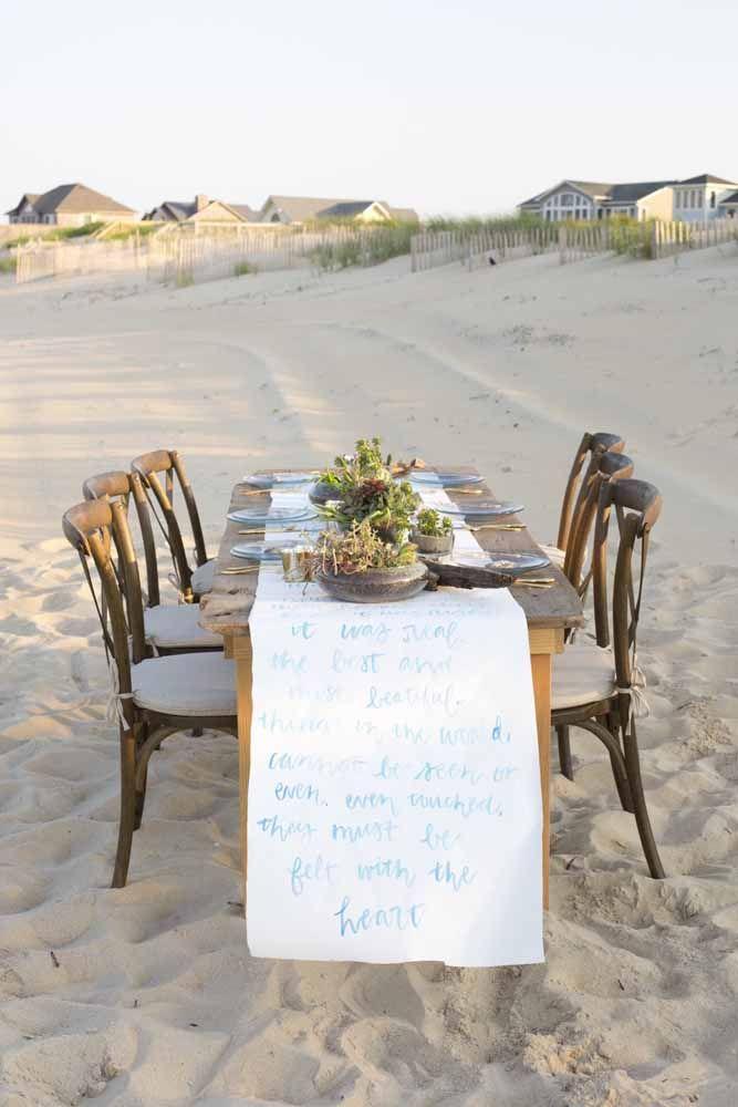Aqui, a toalha de mesa recebeu uma mensagem inspiradora escrita à mão; sobre ela, vasos rústicos de suculentas