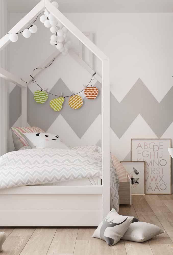 No quarto infantil, a parede foi estampada com um chevron branco e cinza