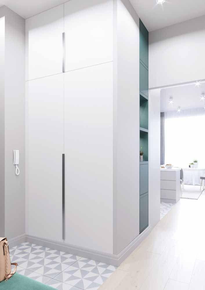 No hall de entrada, o armário alto se confunde com a parede