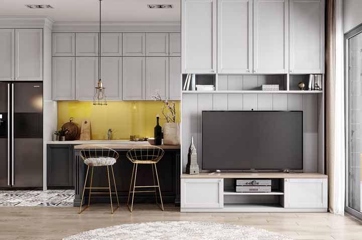 De um lado do móvel, a cozinha, do outro, a sala