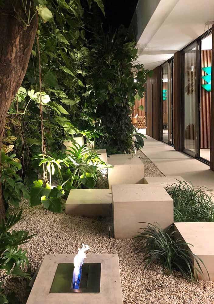 Jardim de folhagens tropicais decorado com uma fogueira artificial.