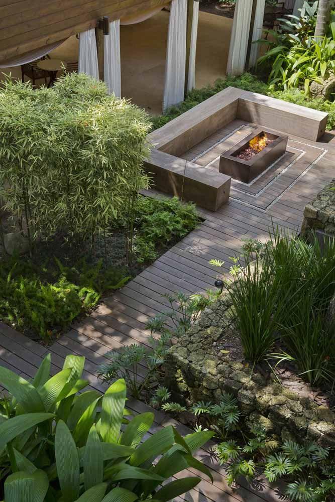 Aqui, o deck de madeira contorna todo o jardim de folhagens