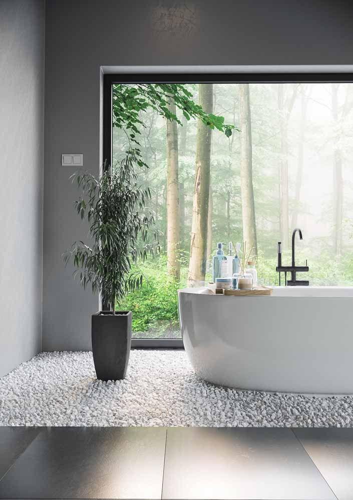 Sobre o chão de pedras, um vaso alto e elegante de bambu