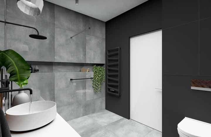 O vaso de dinheiro em penca cria um contraste forte e harmonioso no banheiro de tons escuros