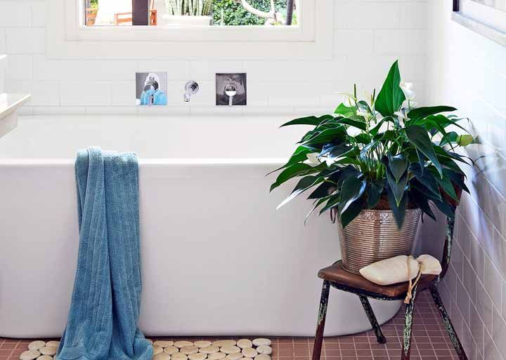 Junto a banheira, o vistoso vaso de lírios da paz dá aquela força para decoração