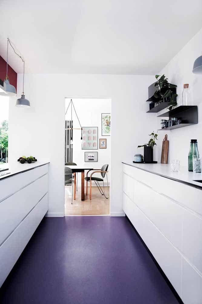 Na cozinha branca, o piso azul de resina epóxi se destaca