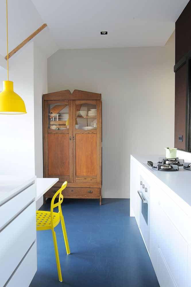 Sobre o piso azul, cadeiras amarelas para criar contraste e para o restante do ambiente, o branco