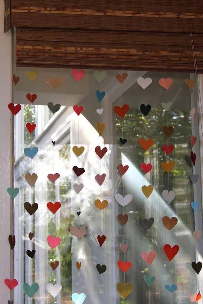 Aqui, a cortina de coração foi usada para a decoração da casa; repare que os corações coloridos ficam junto à persiana de madeira