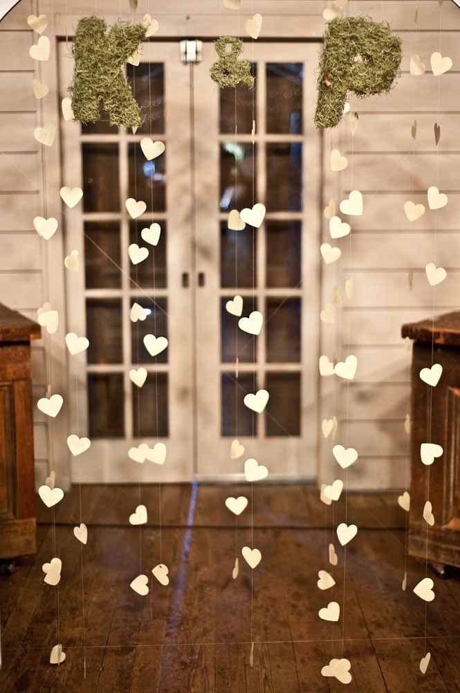 A cortina de corações brancos traz as iniciais dos noivos presas a ela