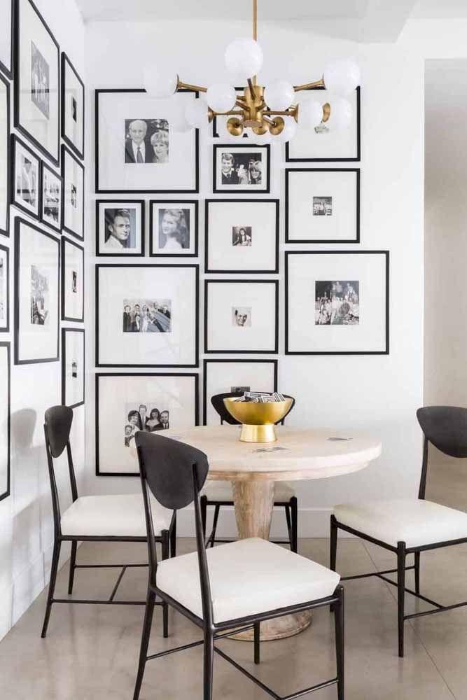 Nessa sala de jantar, as paredes brancas ganharam quadros de fotos que mantem o fundo branco, mas se diferenciam pela moldura preta, combinando com as cadeiras