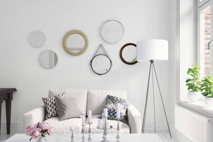 Espelhos com molduras variadas decoram essa parede branca