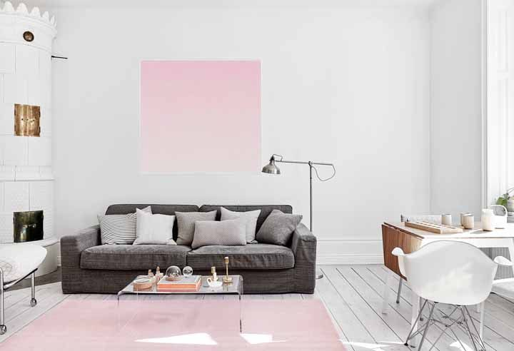 Quadro e tapete cor de rosa em meio ao fundo branco da sala de estar