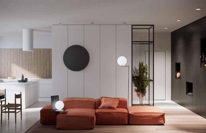 Se a ideia é manter a parede branca complemente a decoração com objetos que tenham cor, como esse sofá de tom terroso
