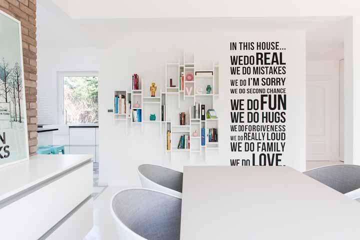 Nessa casa de ambientes integrados, a decoração das paredes brancas incluem nichos, adesivos e tijolinhos aparentes