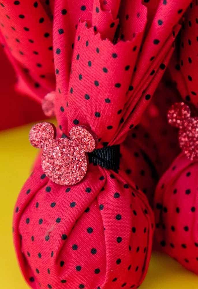Compre um tecido vermelho com pingos preto, coloque o brinde dentro e amarre com um detalhe personalizado