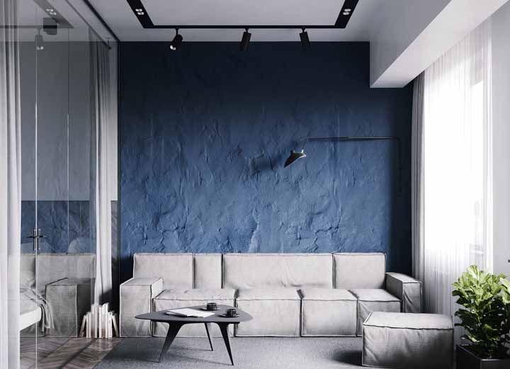 O azul escuro da parede ajuda a realçar o acabamento rústico