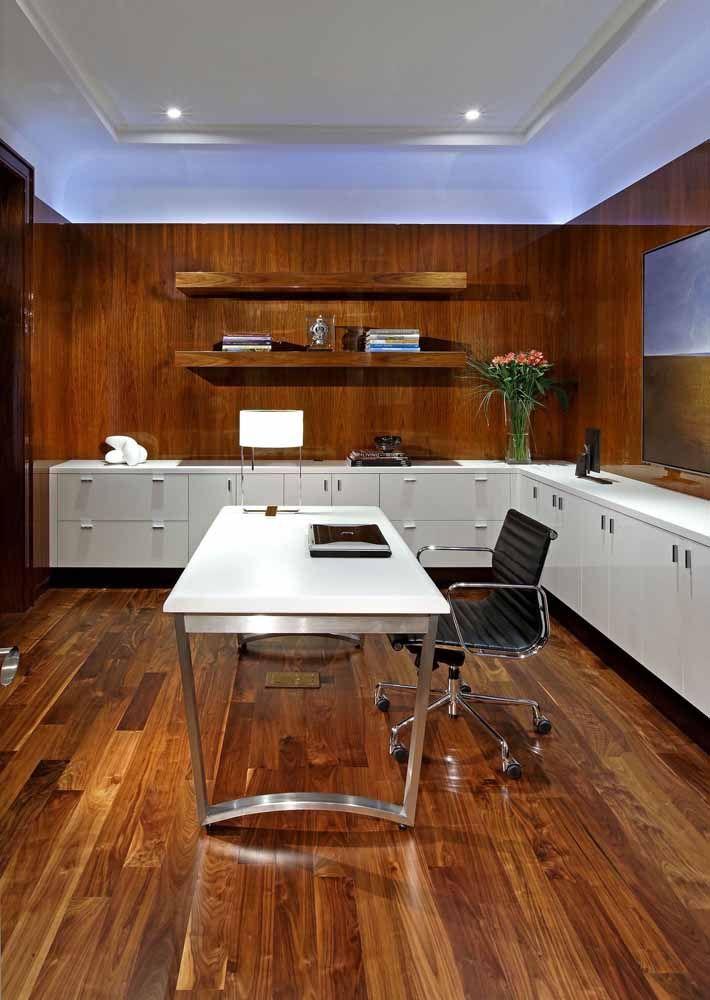 O escritório todo em madeira apostou no uso de uma escrivaninha branca para se destacar