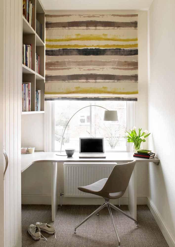 Junto à janela, essa escrivaninha branca de canto forma uma parceria charmosa com a persiana de rolo colorida