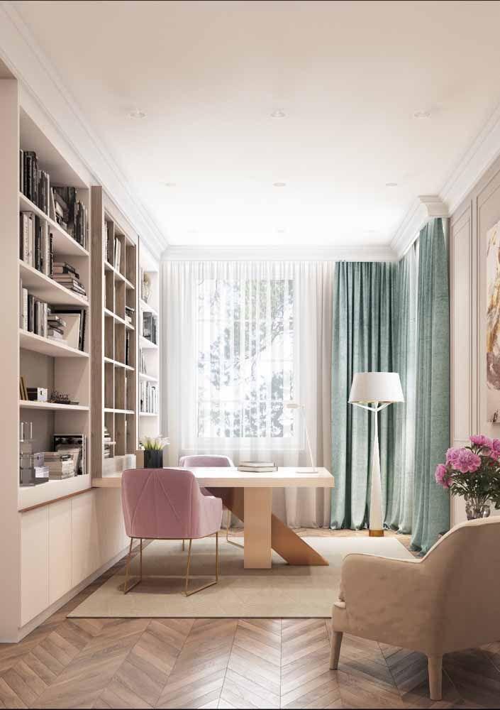 O escritório elegante conta com uma escrivaninha de madeira com detalhe diferenciado na base; as poltronas confortáveis completam a proposta