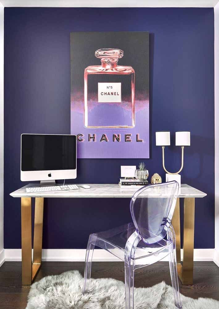 A parede azul escuro realça a escrivaninha branca no ambiente