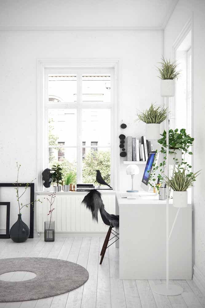 No ambiente branco, a escrivaninha quase nem aparece, são as plantas que revelam sua existência ali