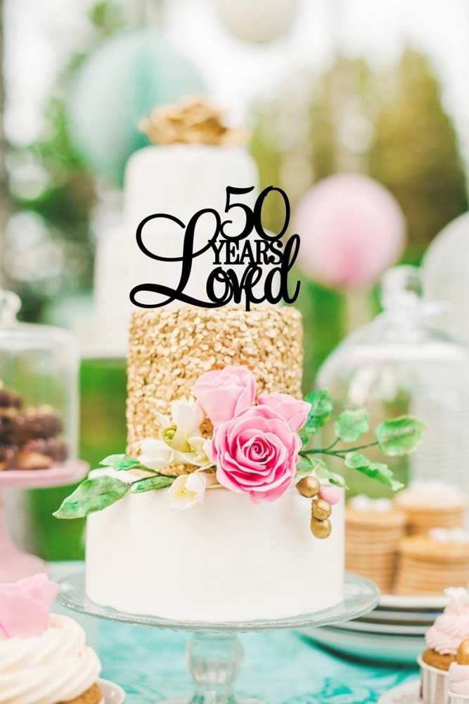 Aqui, as bodas de ouro foi comemorada com um bolo simples dourado e branco