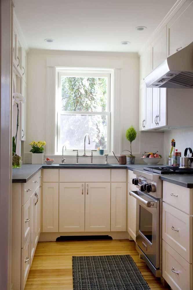 O preto e branco do tapete acompanha a composição de cores da cozinha