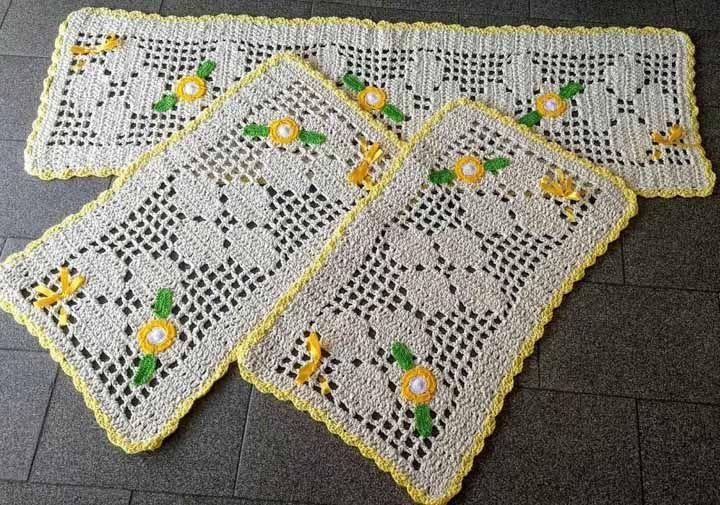 Flores e fitas de cetim dão o toque final para esse tapete de crochê