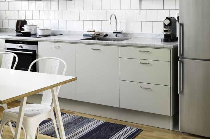 A cozinha branca pode ter um tapete em cor diferente, como o azul, por exemplo