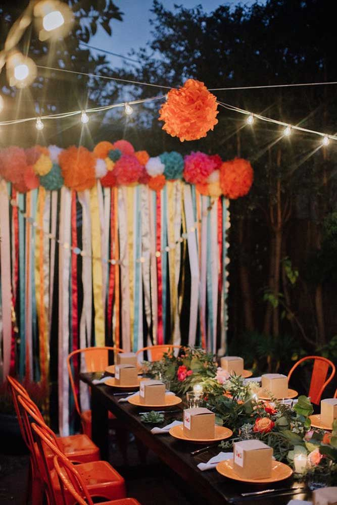 Uma festa à fantasia colorida e em meio à natureza: a iluminação amarelada garante o clima aconchegante para a comemoração
