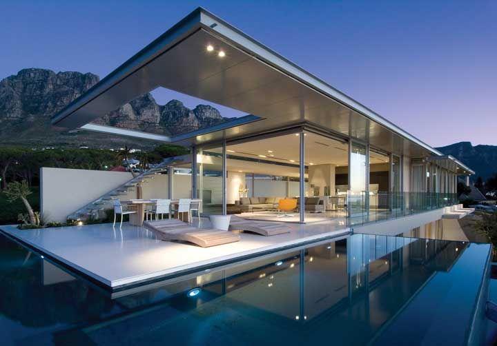 Uma casa de reflexos e transparência graças ao vidro na fachada, a piscina e ao vão no telhado