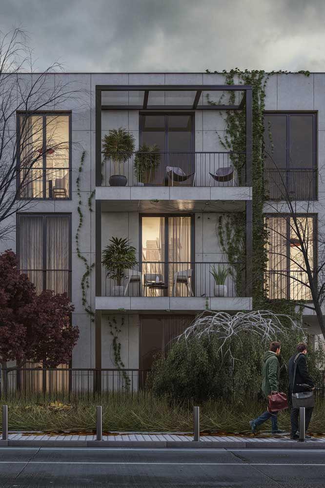 Nessa fachada, os materiais brutos como o concreto e o ferro convivem harmoniosamente com a delicadeza das plantas
