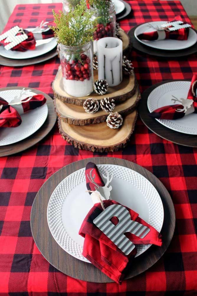 Para completar o charme da toalha xadrez, um centro de mesa para natal feito com cortes de madeira, pinhas e velas