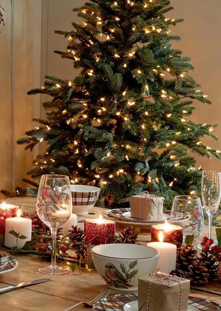 Com a árvore de natal aos fundos, essa mesa de natal rústica apostou em um enfeite baixo feito com pinhas e velas