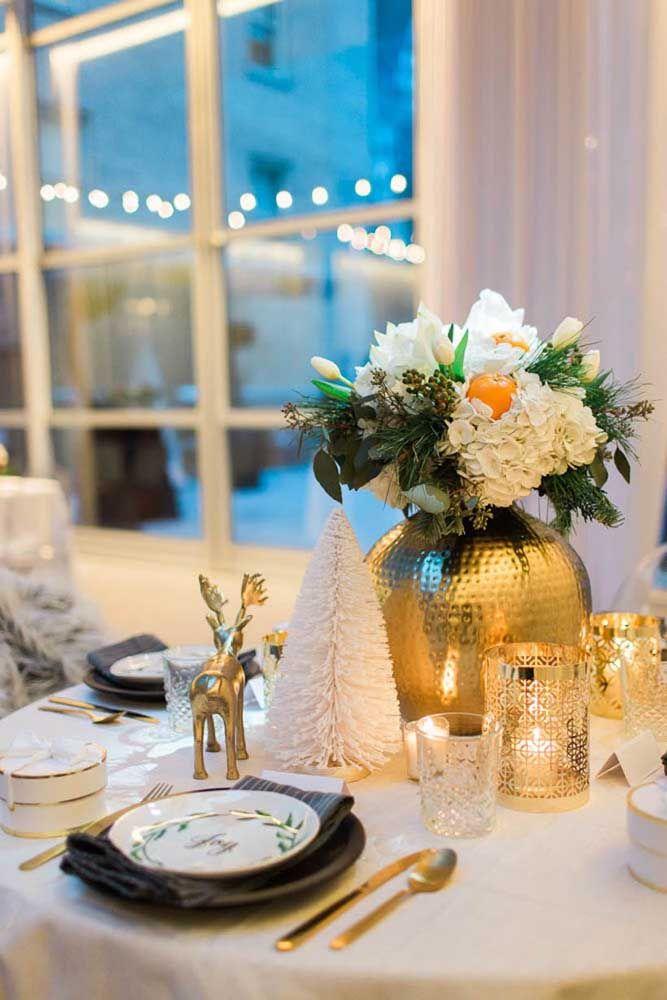 Um elegante e charmoso vaso dourado com flores brancas foi o enfeite de natal escolhido para essa mesa