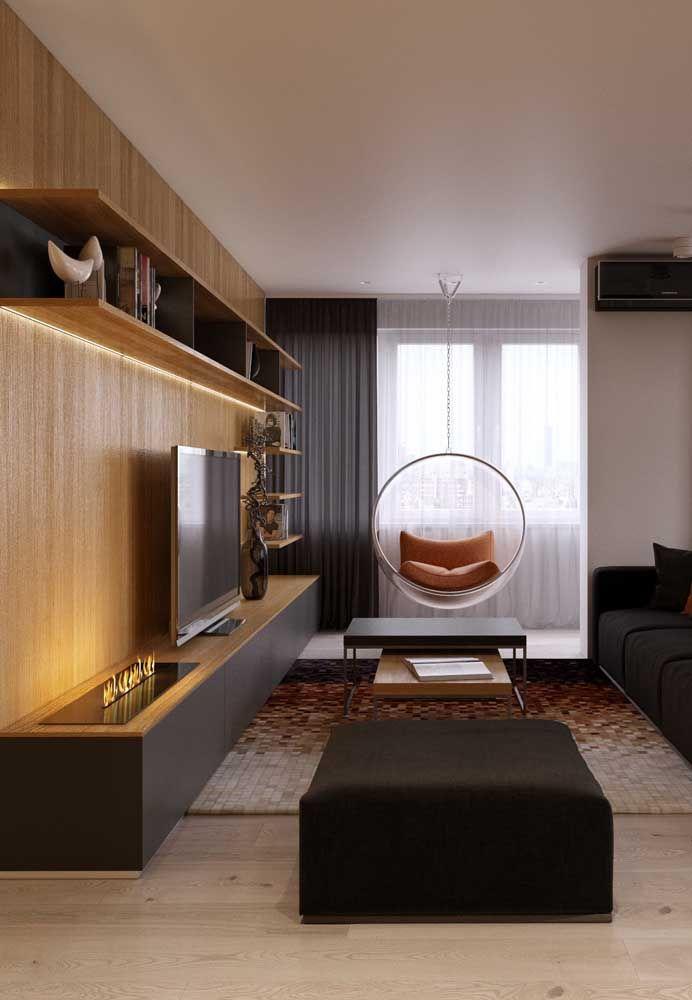 Tons de madeira diferentes no piso e na parede; entre eles o preto dos móveis