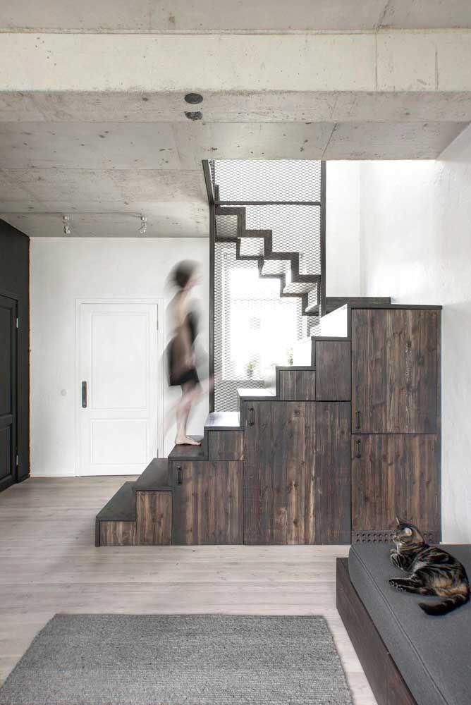 Madeira escura e rústica para completar a decoração industrial da sala; no chão, o piso de madeira claro passa sem chamar atenção