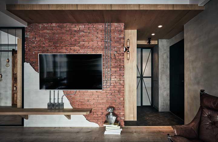 A decor rústica e industrial apostou no uso da madeira clara para criar destaque frente a parede de tijolinhos